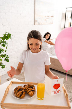 happy child standing near tray with breakfast, mothers day card with heart sign and mom lettering, while mother sitting in bed