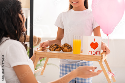 cropped view of child holding tray with breakfast, mothers day card with heart sign and mom lettering near mother sitting in bed