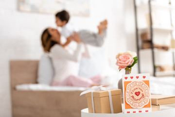 selective focus of mothers day card with i love you mommy inscription and gift box on table, and happy woman having fun with son in bed