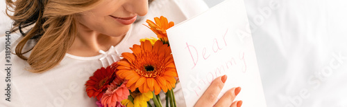 cropped view of happy woman holding bouquet of gerberas and mothers day card, panoramic shot