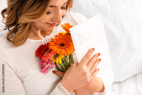 happy woman smiling while holding bouquet of gerberas and mothers day card