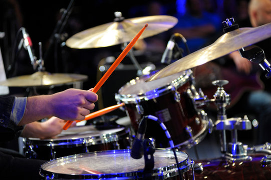 Musician hands holding drumsticks playing drums, marching cymbals