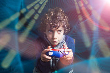 Gamer Kid. 7-8 years old child holding a console game controller playing a video game in a computer graphic light composition ambient. Studio shot. Gaming addiction concept.