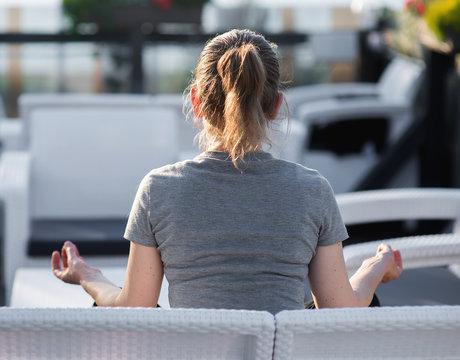 Mature Woman Meditating While Sitting On Sofa