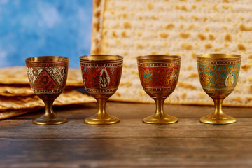 Four wine cups with matzah. Jewish holidays Passover.