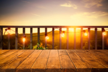 Fototapete - Wooden board of free space for your decoration. Blurred background of balcony and ladnscape of Tuscany.Small lights and orange color of sunset time.