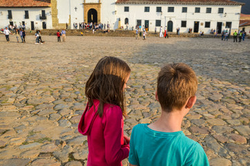 siblings walking through a colonial stoned plaza in Colombia