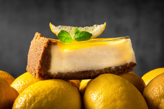Lemon cheesecake slice with fresh mint leaf is placed on yellow ripe lemons with grey background. Beautiful, delicious cake on creative background. Dessert close up, side view