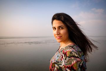 A portrait of smiling beautiful iranian persian girl outdoor on the beach looking at camera