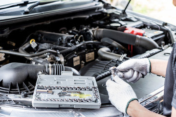 Mechanic male  worker using  with ratchet  socket wrench block tool during car repair works in auto service center