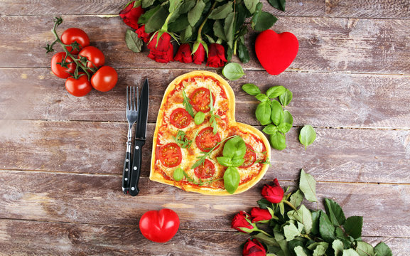 pizza Heart shaped margherita with tomatoes and mozzarella vegetarian. Food concept of romantic love pizza for Valentines Day.