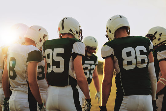 American football players standing in a huddle before a game