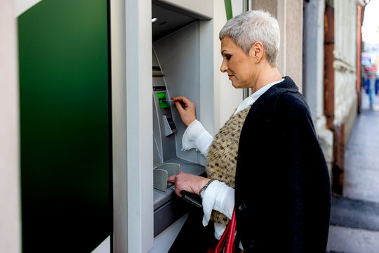 Middle age woman is withdrawing money from ATM machine