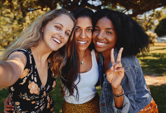 Portrait of three smiling happy multiethnic female friends taking a selfie in the park on a sunny day