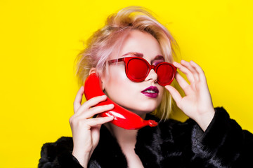 Portrait of a glamorous blonde in a fur coat with a red banana and sunglasses. The blonde is talking on a banana on a yellow background.