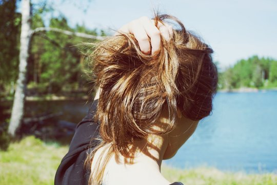 Rear View Of Young Woman With Hand In Hair Standing At Lakeshore Against Sky