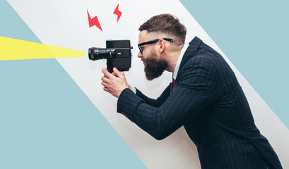 Filmmaker with a vintage lomo camera. Professional Videography. Man with beard in trendy formal...