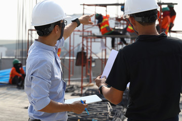 Two engineers work on the construction site. They are checking the progress of the work.