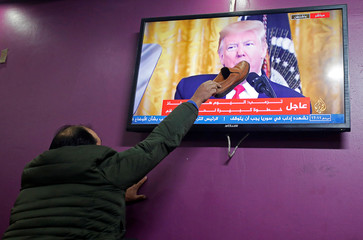A Palestinian man places a shoe on a television screen broadcasting the announcement of Mideast peace plan by U.S. President Donald Trump, in a coffee shop in Hebron in the Israeli-occupied West Bank