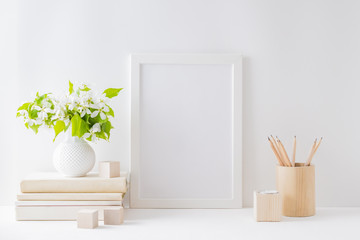 Home interior with decor elements. Mockup with a white frame, spring flowers in a vase on a light background