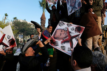 Supporters of Libyan National Army (LNA) commanded by Khalifa Haftar, hold a picture of Turkish President Tayyip Erdogan as they celebrate on top of a Turkish military armored vehicle, which LNA said they confiscated during Tripoli clashes, in Benghazi