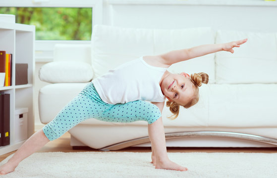 Cute little child girl making morning exercises at home