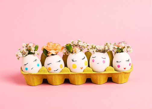Easter creative concept. Easter decorative eggs with painted cheerful faces and flowers instead of hair in the cardboard egg tray on the pink backgraund. Copy space