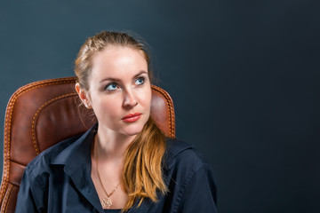 Beautiful blonde girl looking up at someone from bottom to top, sitting in a chair in a black mantle