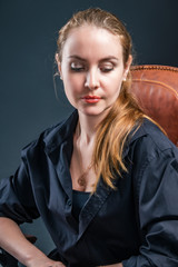 Beautiful blonde girl with her eyes lowered, sitting in a chair in a black mantle