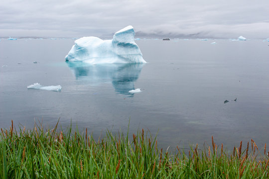 An iceberg floats in the harbor of a small Inuit village in Greenland