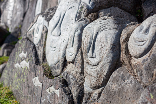 Stone faces of Inuits sculpted on a stone in Qaqortoq. Greenland