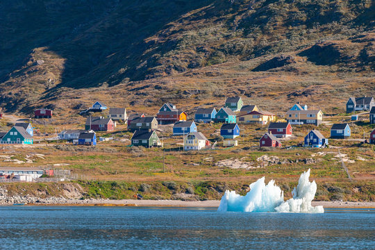 View of a small Inuit village from the sea with floating icebergs.