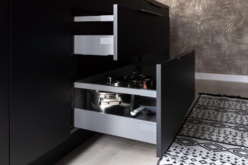 Opened drawers with pots and pans inside in a black kitchen. Storage solution.