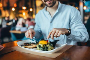 close up of man having lunch in restaurant Fototapete
