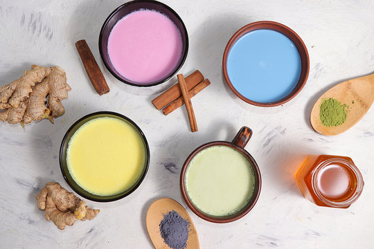 An assortment of colorful latte Japanese tea, matcha green, blue, pink moon milk, golden milk, ginger and cinnamon, top view. A fashionable healthy drink has anti-inflammatory properties.
