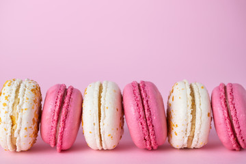 Türaufkleber Macarons French delicious pink and white macarons of different flavors on pink pastel background.