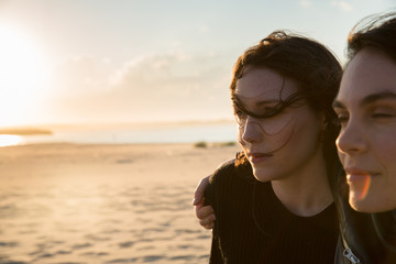 millennial woman on beach during sunset 20s hair in face
