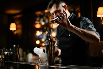 Male bartender flows alcohol from small jigger to shaker