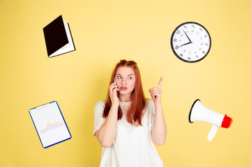 Pointing, talking. Caucasian young woman's portrait on yellow studio background, too much tasks. How to manage time right. Concept of working, business, finance, freelance, self management, planning.