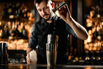 Poster de jardin Bar Male bartender drops alcohol from jigger to cocktail shaker
