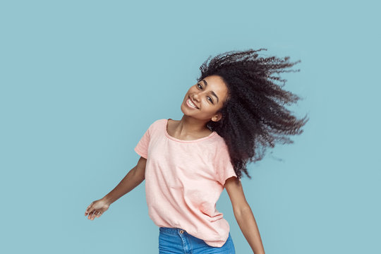 Freestyle. African girl standing isolated on gray shaking head cheerful