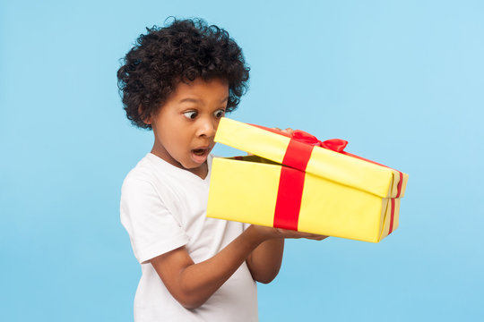 Portrait of amazed curious adorable little boy peeking inside gift box, unpacking present with funny astonished expression, impatient child unboxing birthday surprise. studio shot blue background