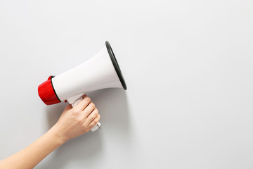Female hand with megaphone on white background