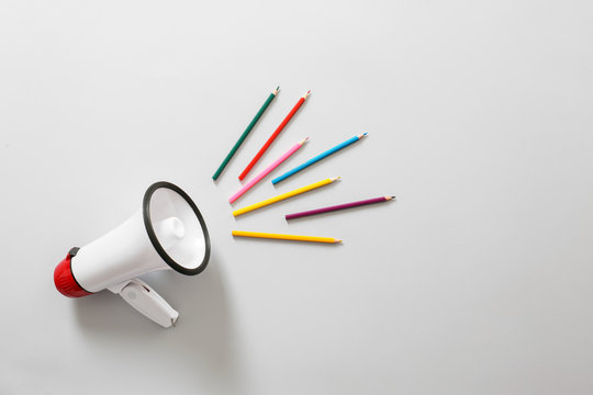 Megaphone with colorful pencils on white background