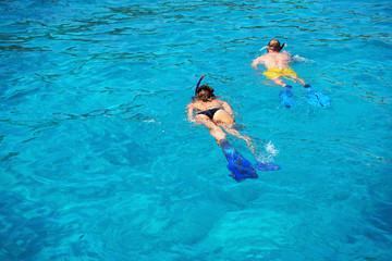 Woman and man dive with flippers and mask in turquoise waters of Aegean Sea, Greece. Wall mural