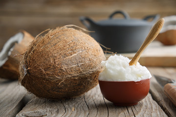 Healthy coconut oil for cooking in ceramic bowl and coconuts on wooden kitchen table.