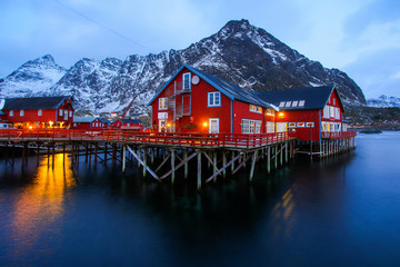 Hotel in the small fishing village of A (Moskenes) at the end of the road of the Lofoten islands archipelago in northern Norway - Red rorbuer on stilts in winter at dawn in a fjord