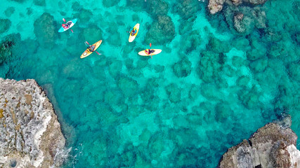 view of a drone from a drone people are kayaking in the sea near the mountains in a cave with turquoise water on the island of Cyprus Ayia Napa Wall mural