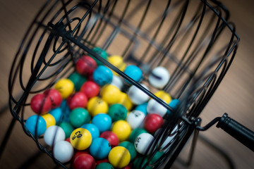 A bingo ball cage with colorful balls inside.