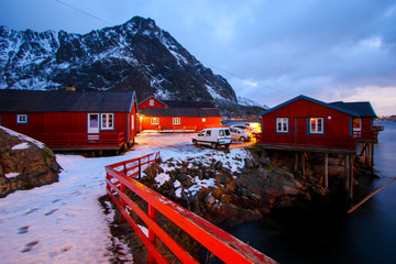 Small fishing village of A (Moskenes) at the end of the road of the Lofoten islands archipelago in northern Norway - Red rorbuer on stilts in winter at dawn